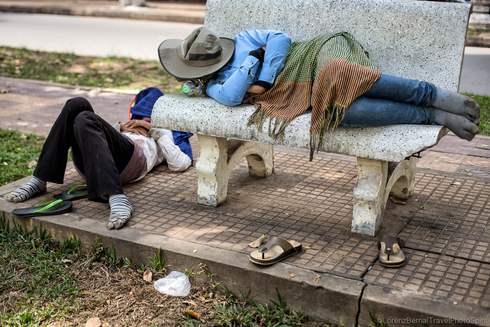 Men sleeping on street benches during a break in Cambodia
