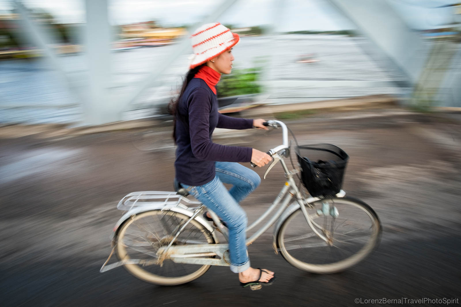 Cambodian girl cycling on Kampot old bridge, Cambodia - Lorenz Berna travel photography.