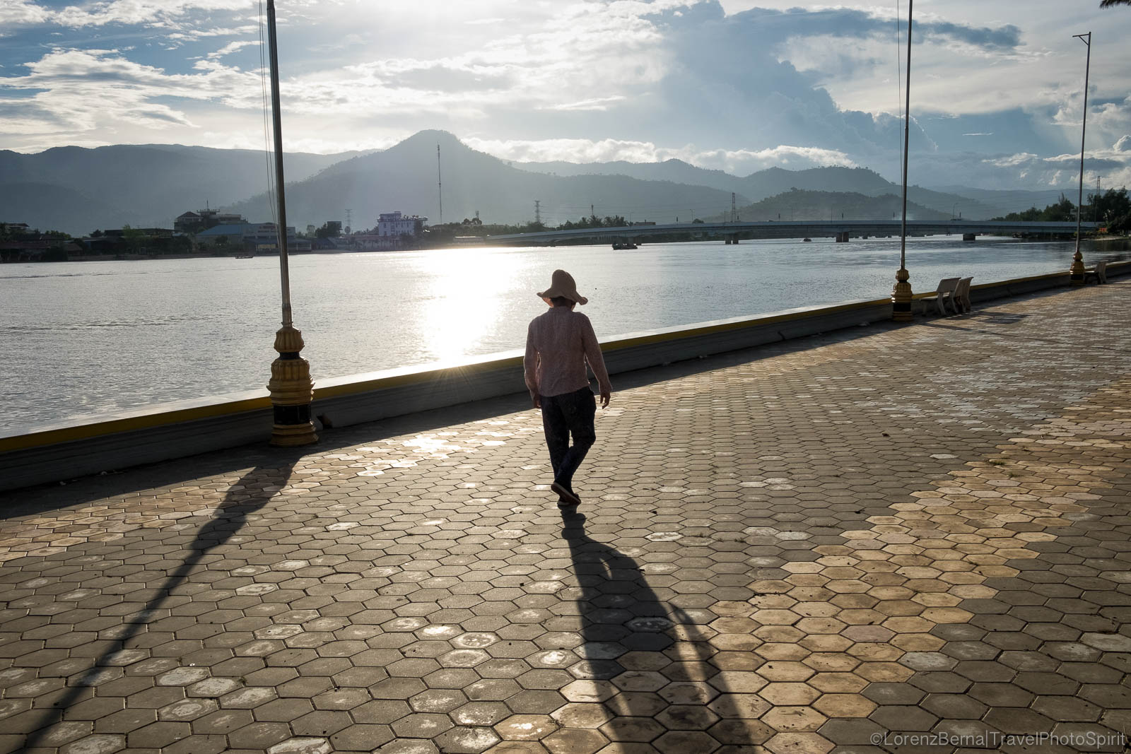 Woman walking on Kampot riverside with Bokor National Parc in background, Cambodia