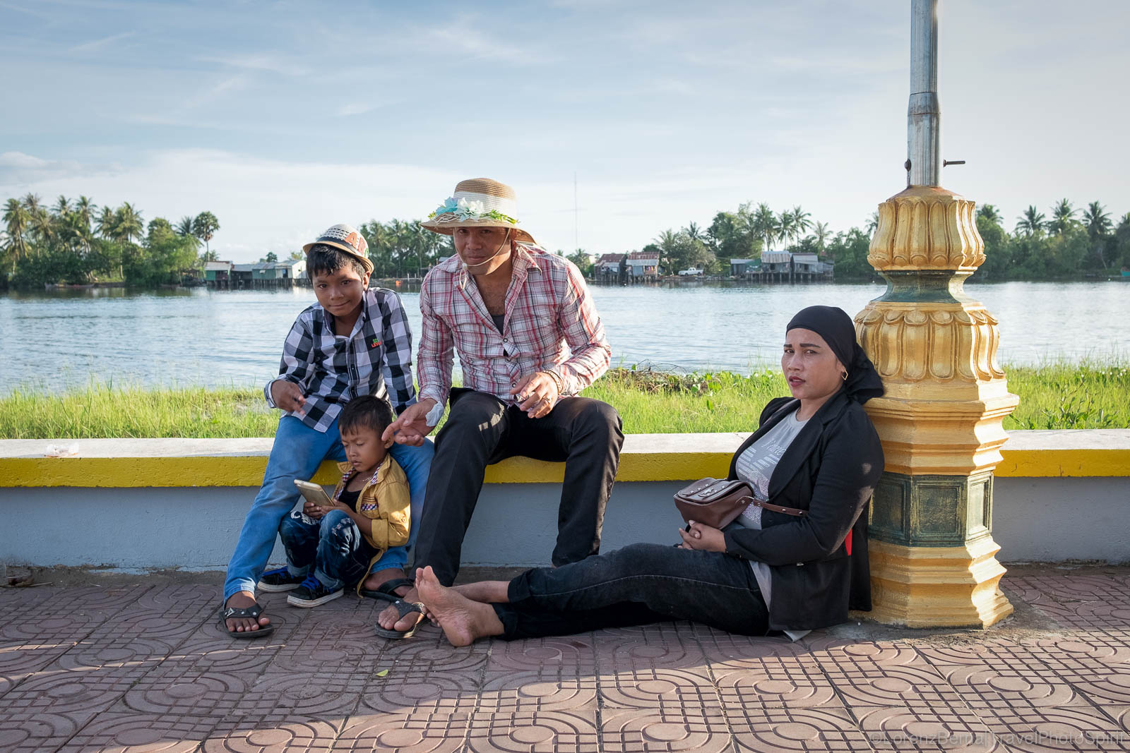 Muslim Cham family relaxing on the riverside on a late afternoon, Cambodia