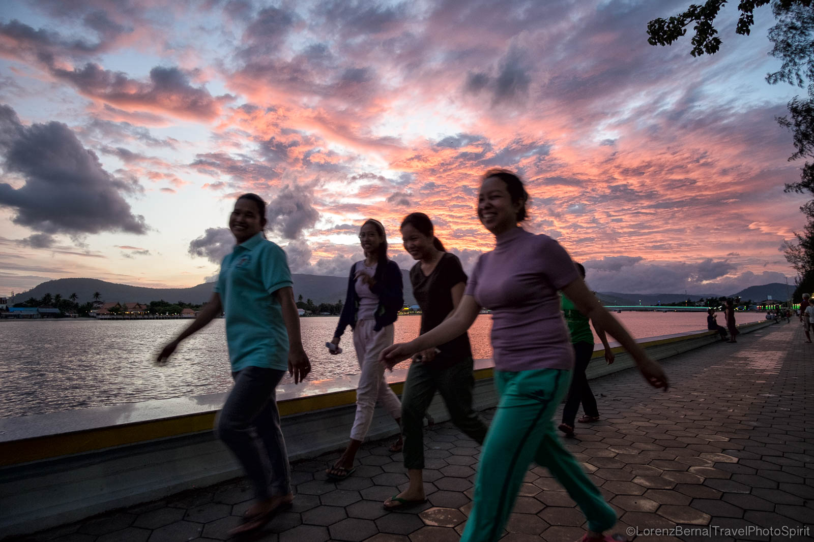 Group of women on an evening walk exercise on Kampot riverside, Cambodia.