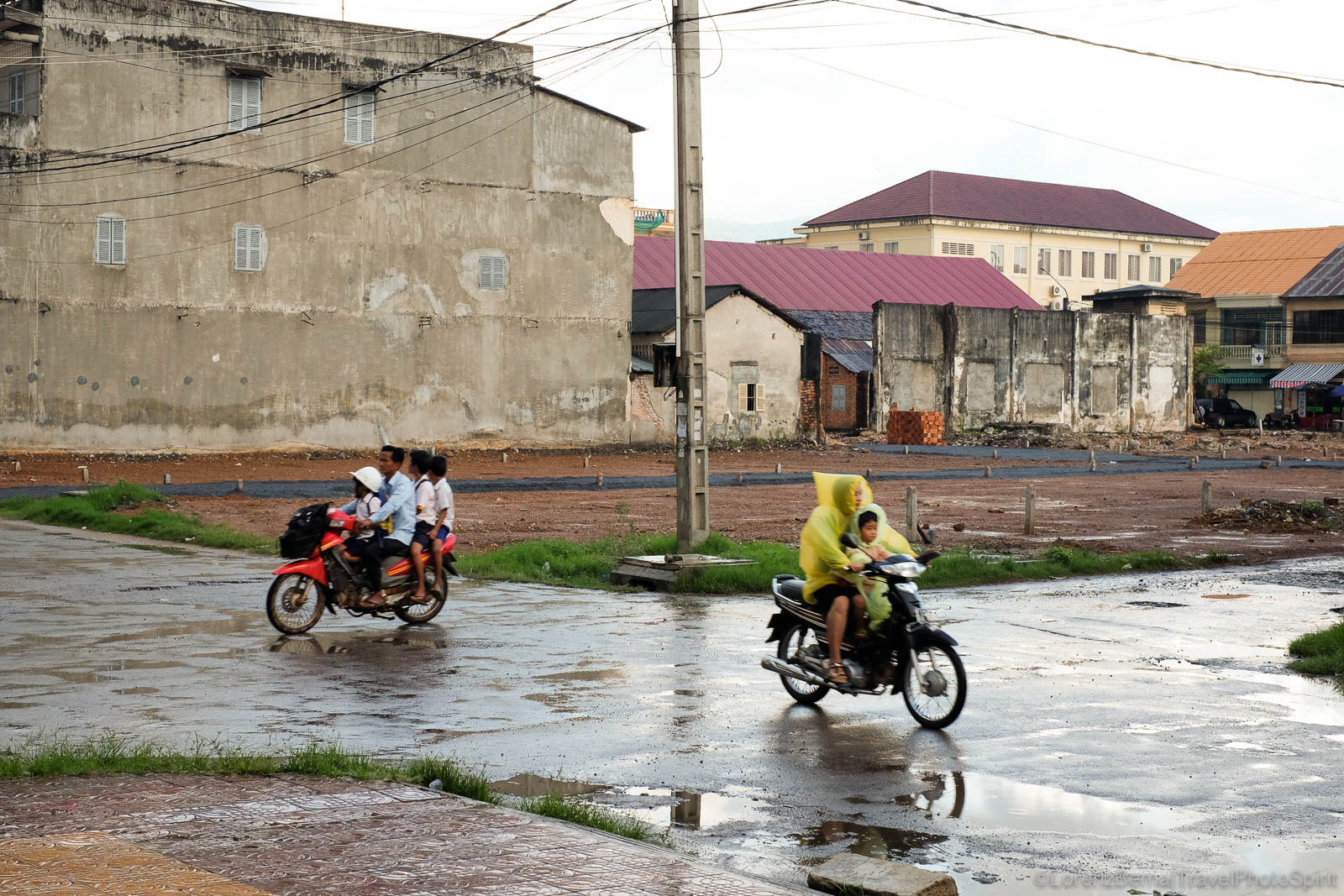 Local people driving under the monsoon rain, in Kampot, Cambodia