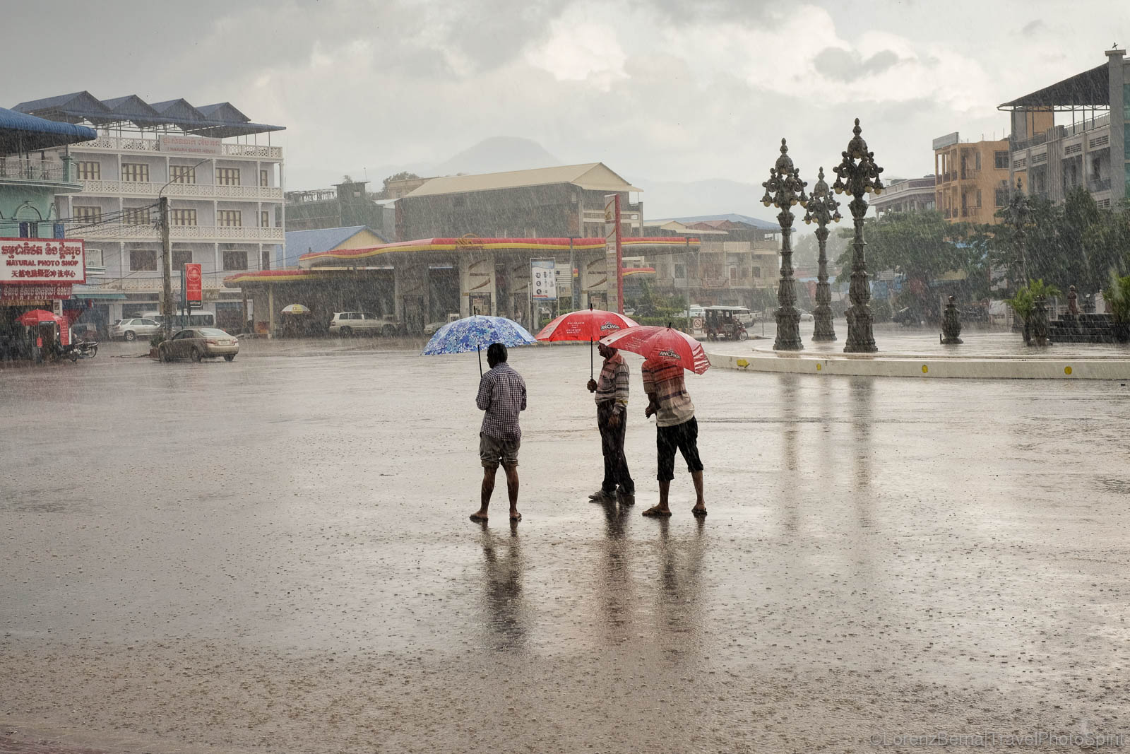 Taxi drivers waiting for customers under the monsoon rain in Kampot, Cambodia