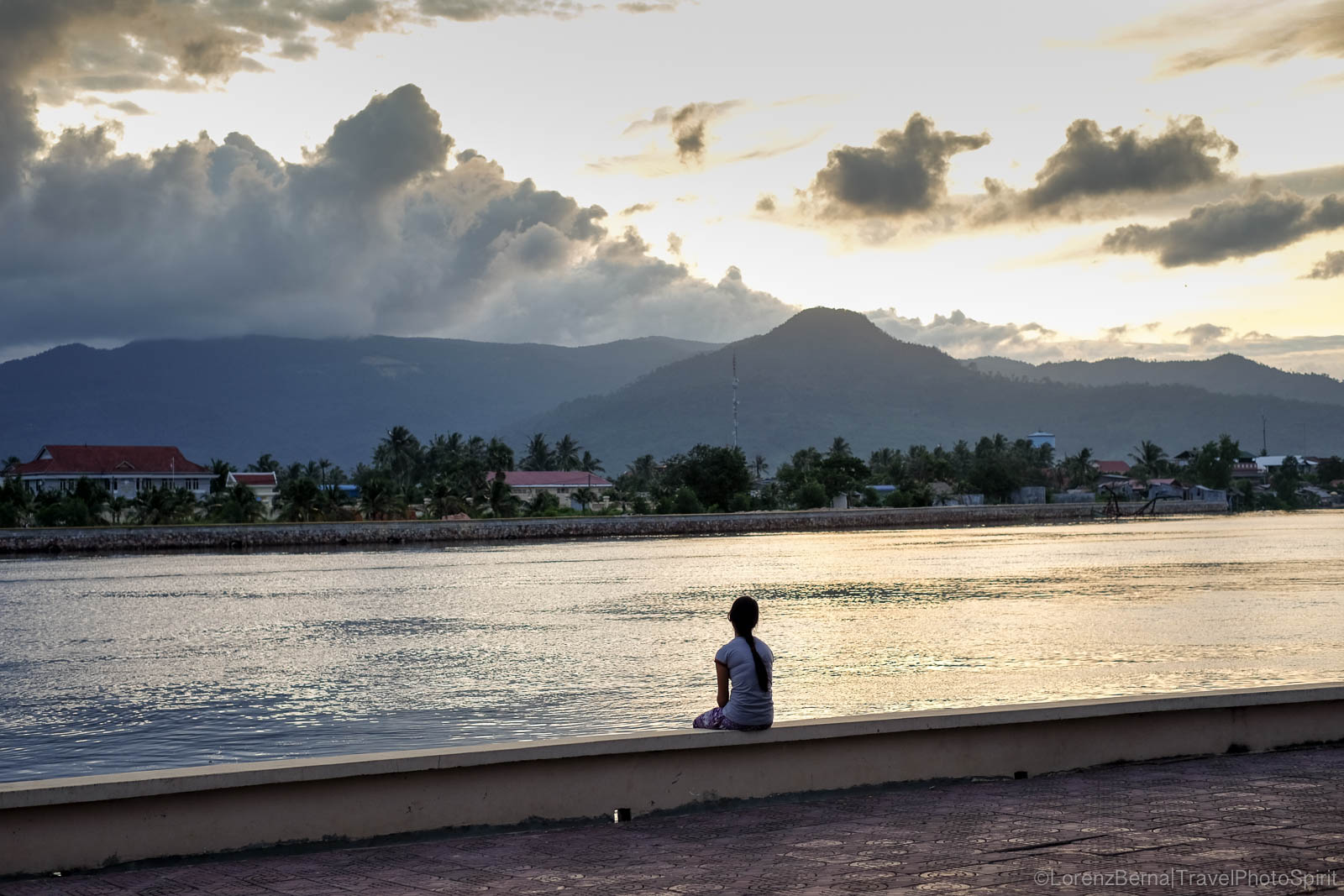 Young woman sitting on Kampot riverside, waiting for the sunset on the Bokor Mountain.