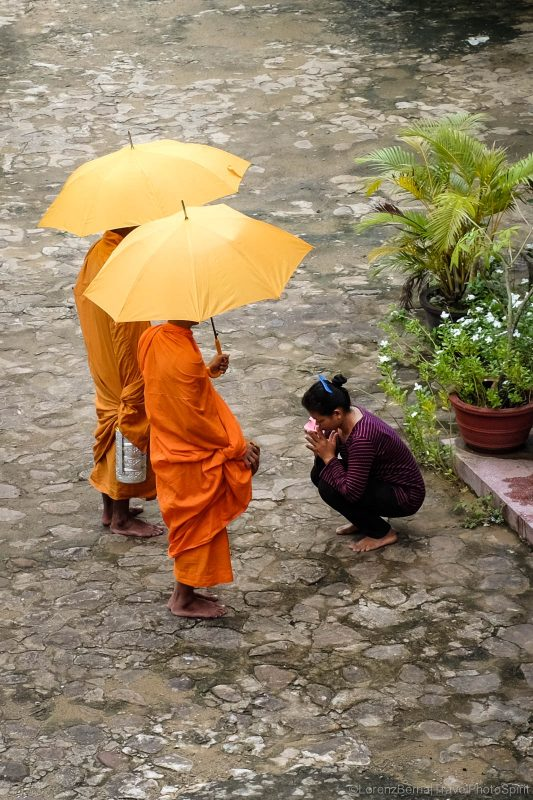 Woman receiving a blessing from two buddhist monks in Kampot, Cambodia