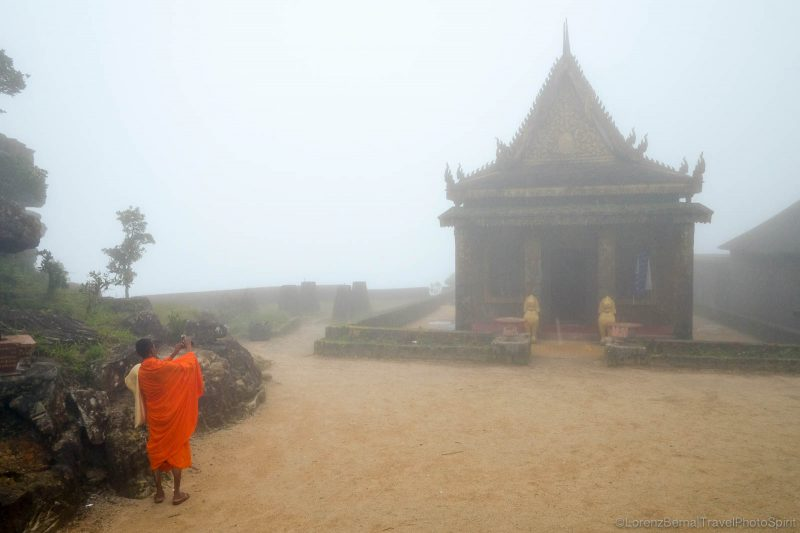 Cambodian monk in front of the Buddhist temple on top of the Bokor National Parc, Kampot region, Cambodia