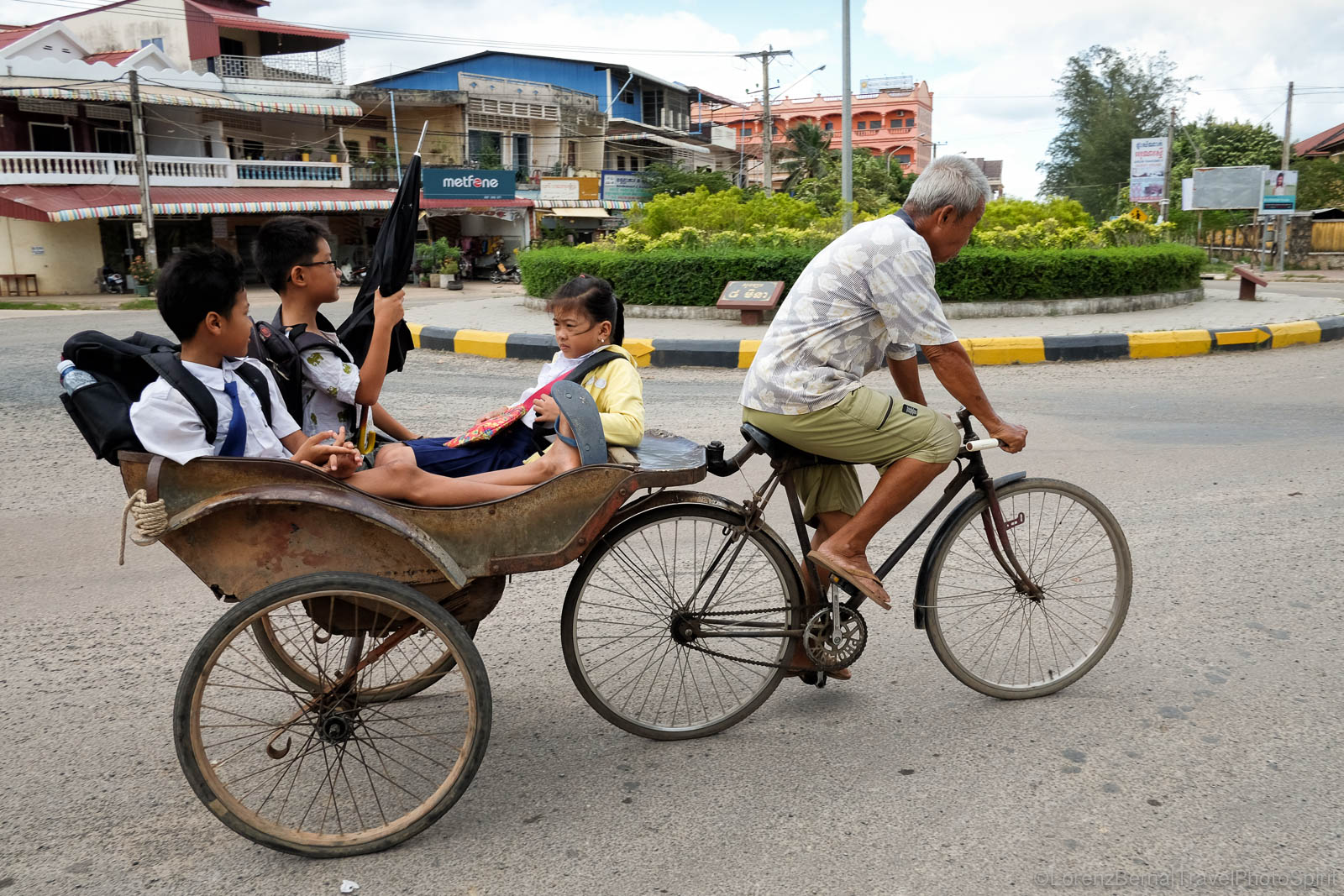 Man driving children at school on a traditional cycling rickshaw in Kampot, Cambodia