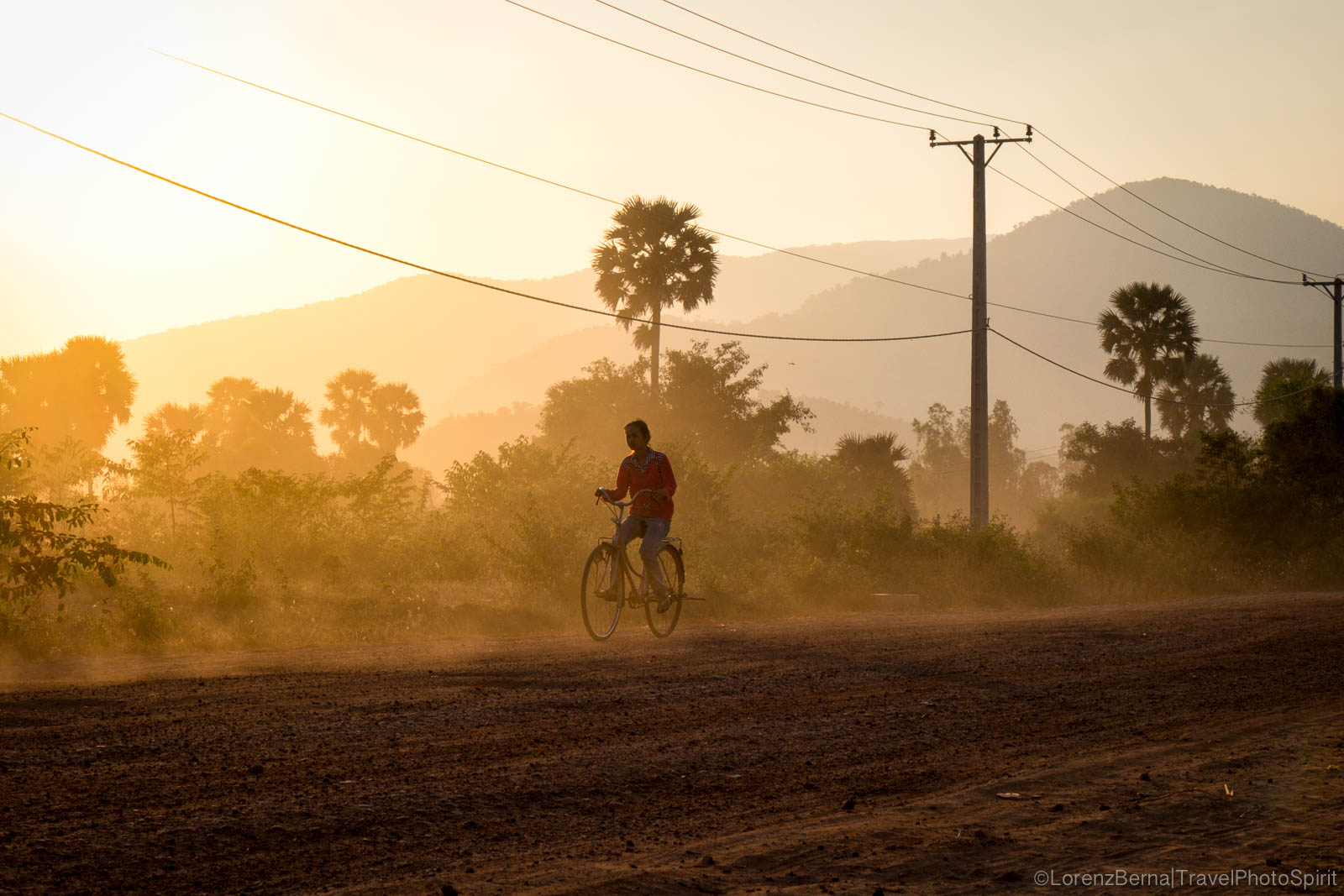 Cambodian child on bicycle in the backlight in Kampot countryside, Cambodia