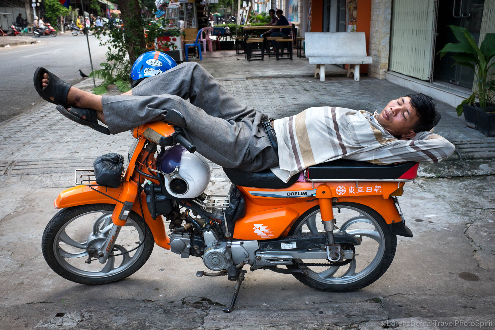 Moto-taxi driver sleeping on his motorbike in Phnom Penh, Cambodia