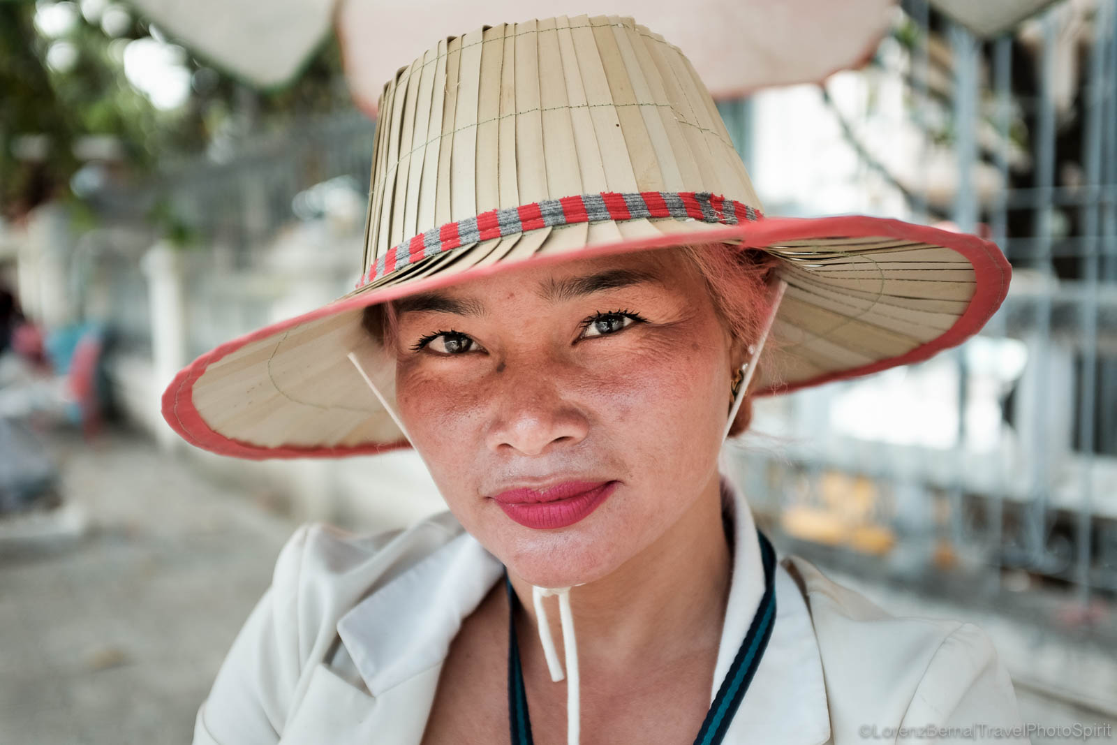 Portrait of a Cambodian woman wearing a traditional hat made with palm leaves.