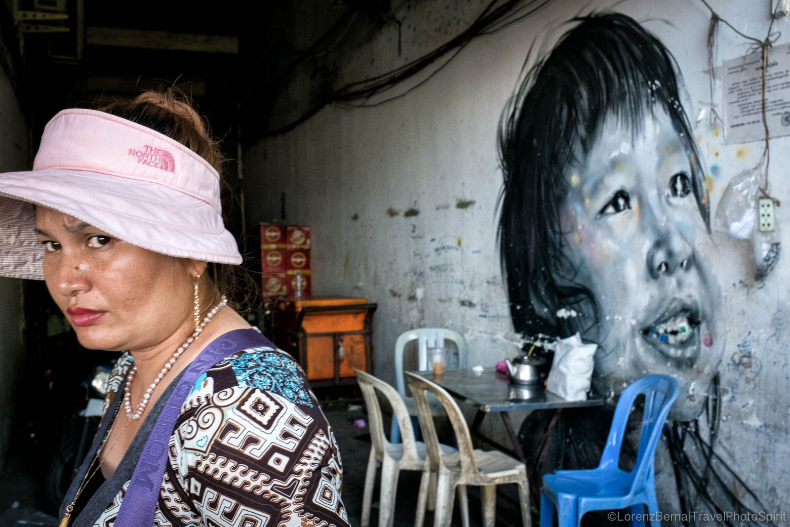 A street food shop settled along a painted mural in Phnom Penh, Cambodia