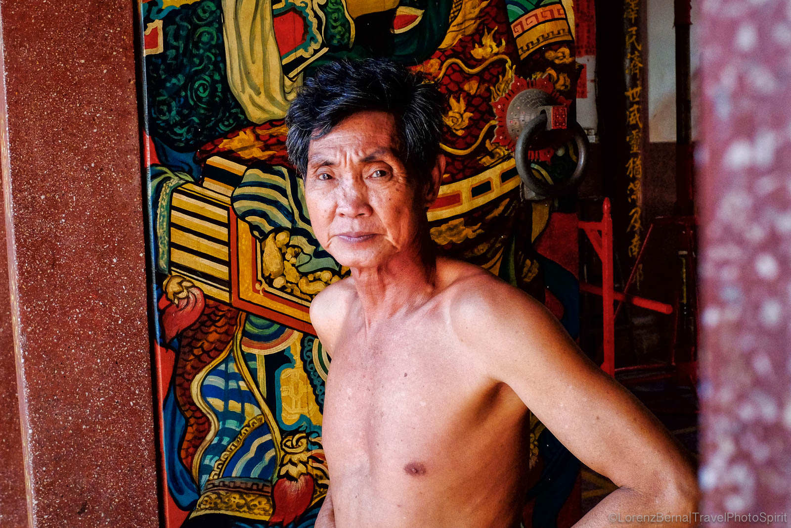 Man in front of the entrance door of Chinese Temple, in Phnom Penh, Cambodia