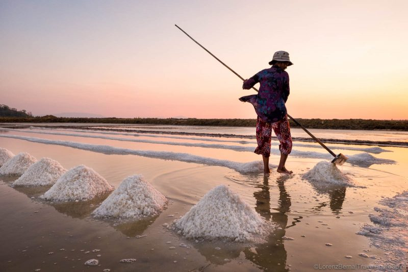 Worker in Kampot salt fields at sunset - A Lorenz Berna travel photography of Cambodia