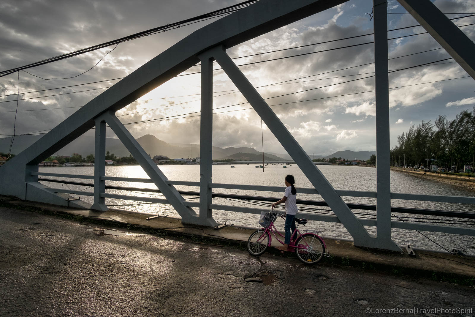 A local girl has stopped to watch the fishermen boats passing under Kampot old bridge, Cambodia