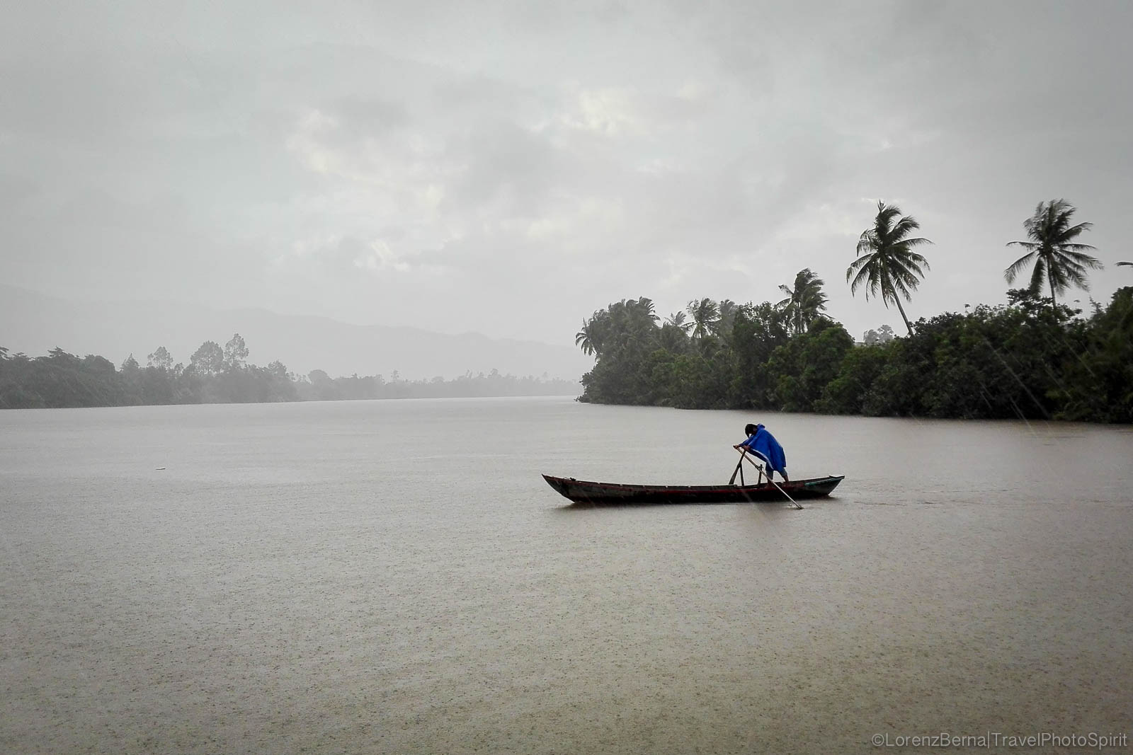 Local fisherman sailing on Kampot River under the heavy Monsoon rain, South Cambodia