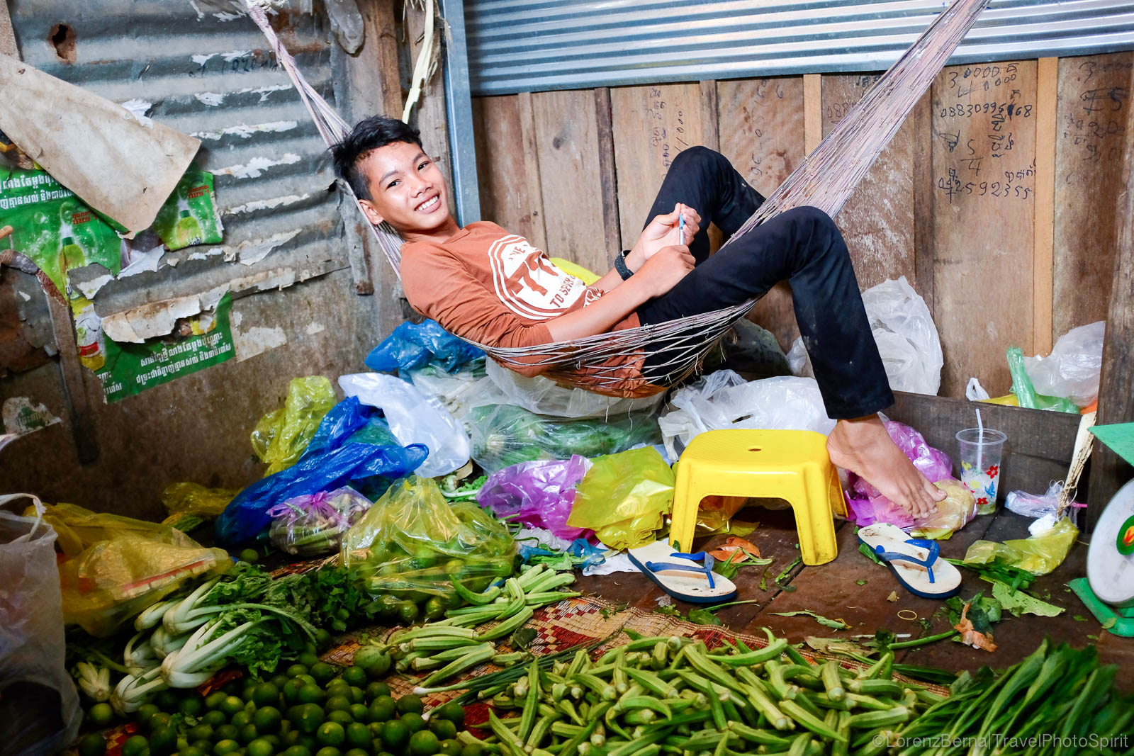 Seller boy in a hammock in a market stall, Cambodia