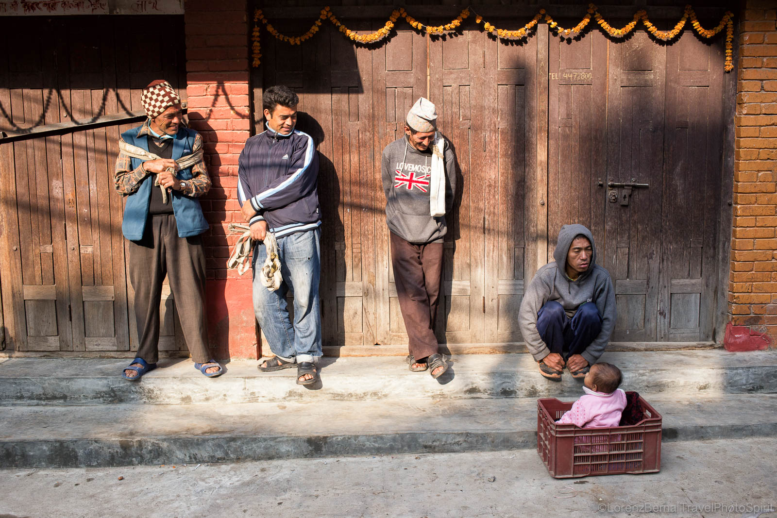 A group of porters enjoying the first rays of sun warming up the streets of Bhaktapur, entertained by a baby playing in a box in front of her father.