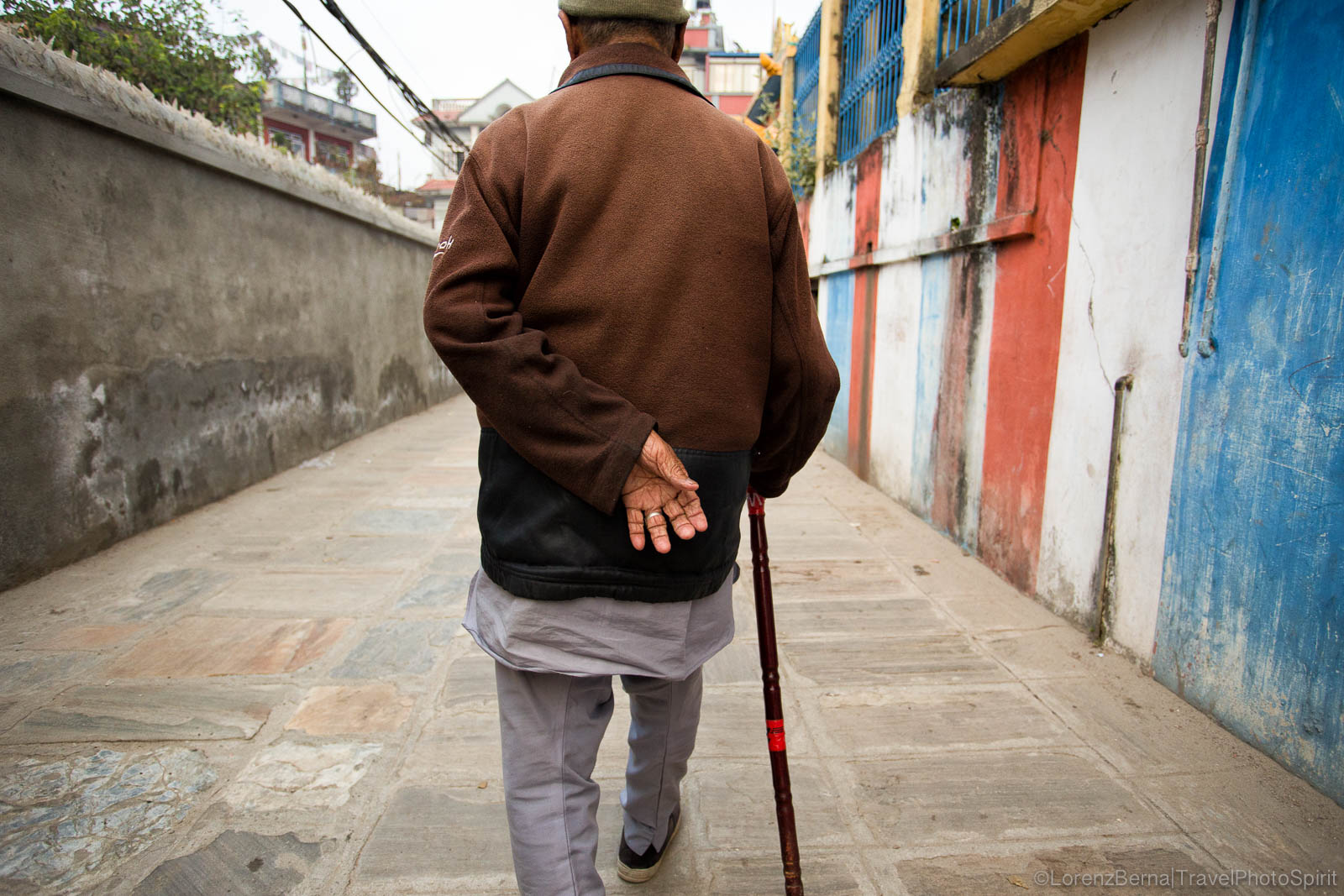 Street Photography in Kathmandu : the back of a local man is walking in a colourful street.