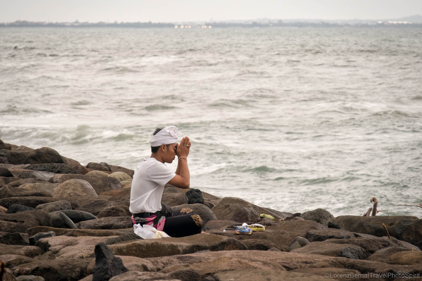Balinese man praying on the rocks of the seashore nearby Tanah Lot, Bali, Indonesia.
