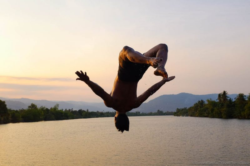 Local man jumping freely in Kampot River by Sunset - A Lorenz Berna Travel Photography of Cambodia