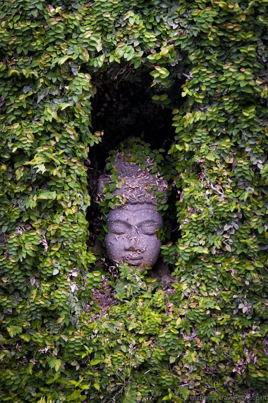Buddha head within a house edge in a street of Bali, Indonesia.