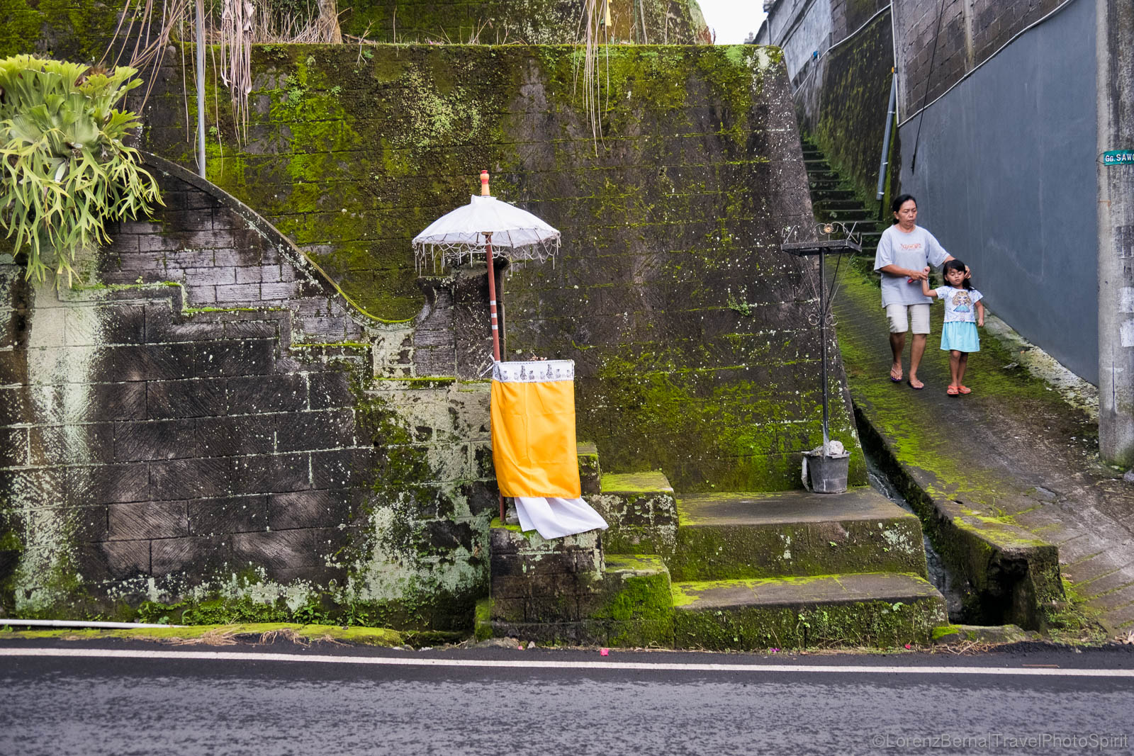 Street detail in Bali : a small altar temple where locals bring water, flower and rice offerings to the Gods, Indonesia.