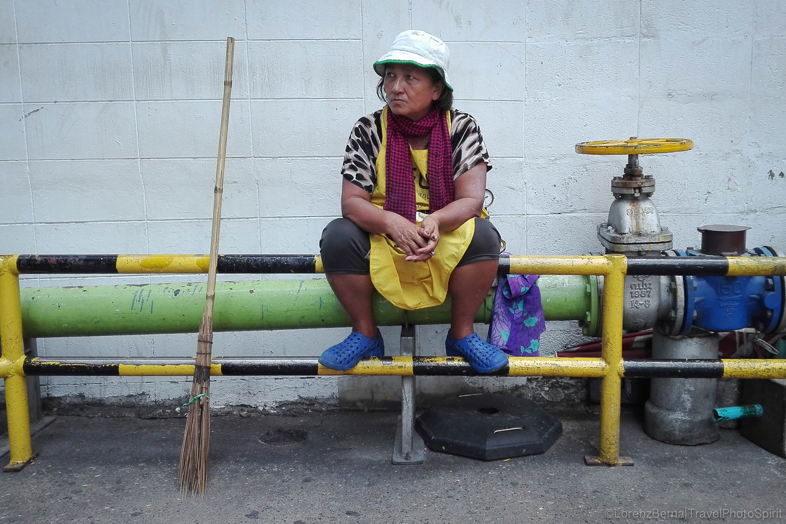 Worker on a break, in the back of a big commercial building in Bangkok.