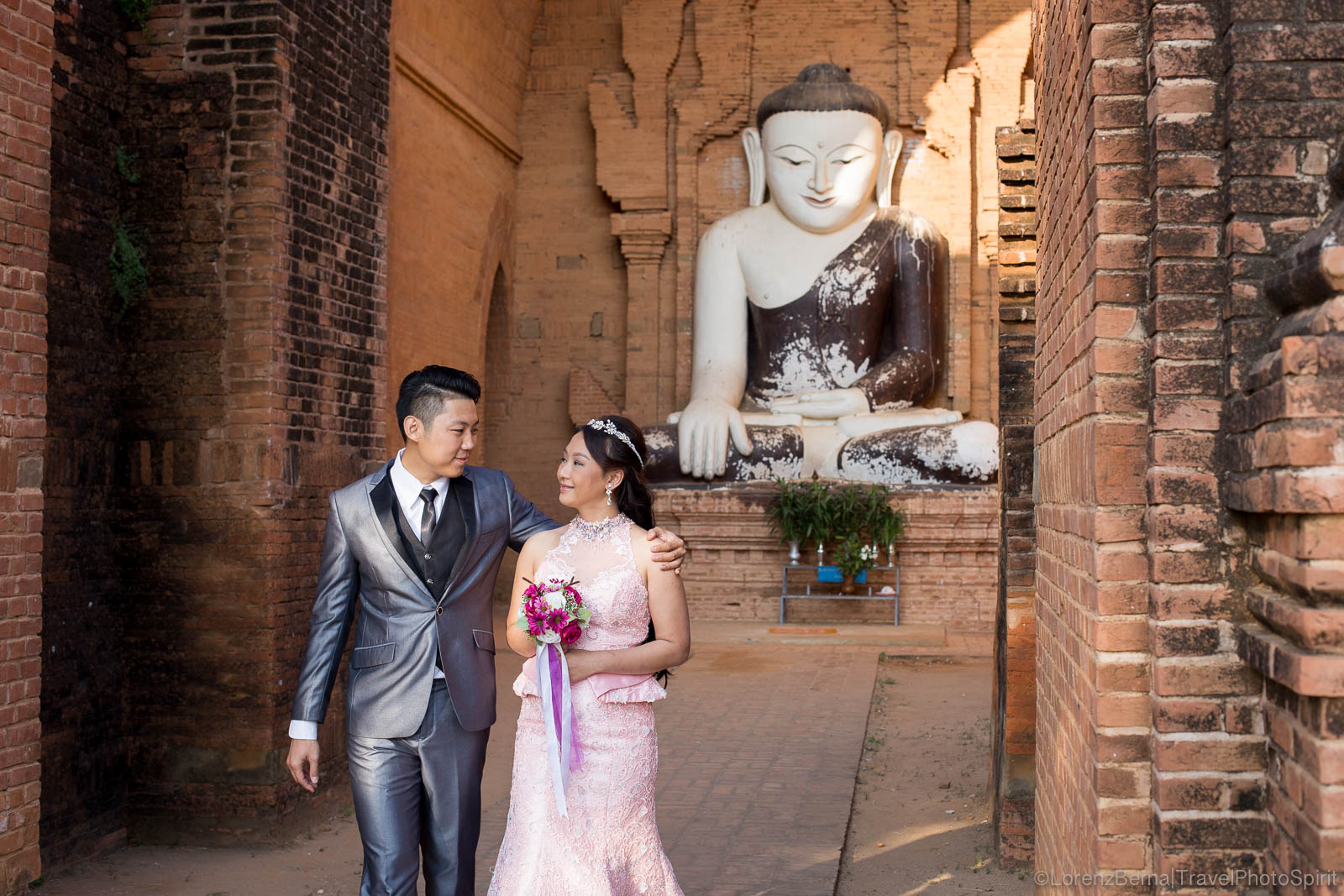 Couple just married, paying homage to the Buddha.