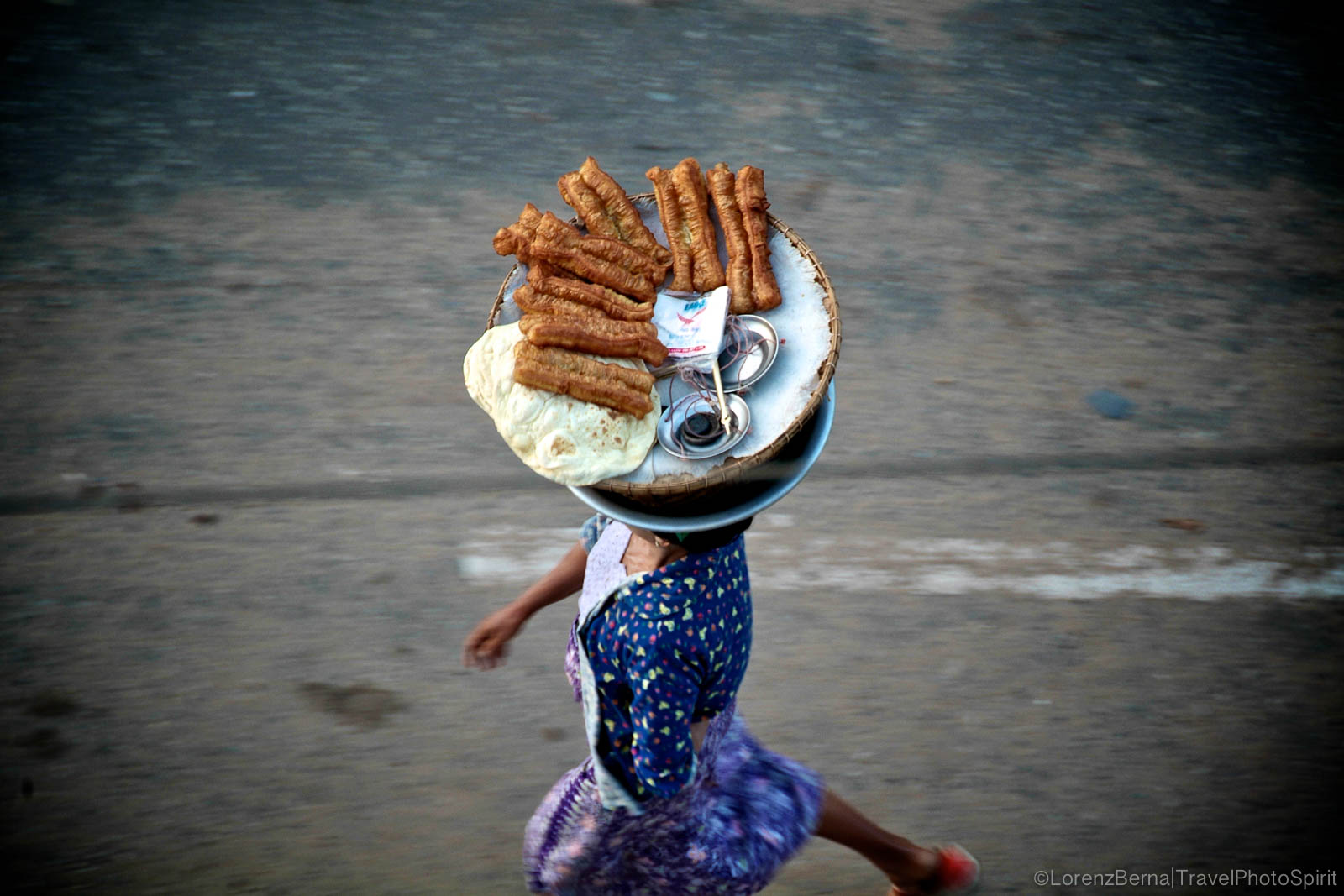 Seller carrying her food tray on her head in Yangon, Myanmar.