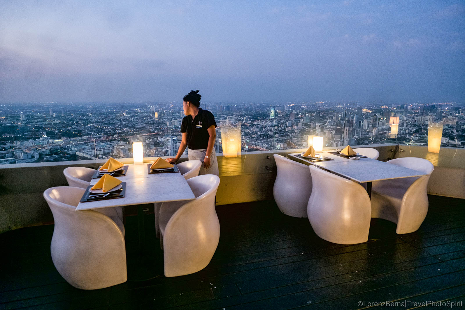 Waitress lost in her thoughts above the city, on the top floor restaurant of the Baiyoke Sky Tower in Bangkok.