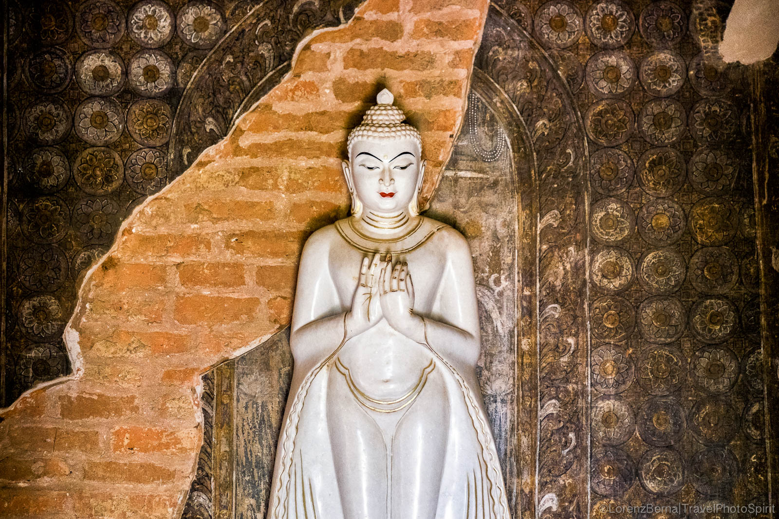 Detail of a statue of Buddha set along an old painted wall inside some pagoda.