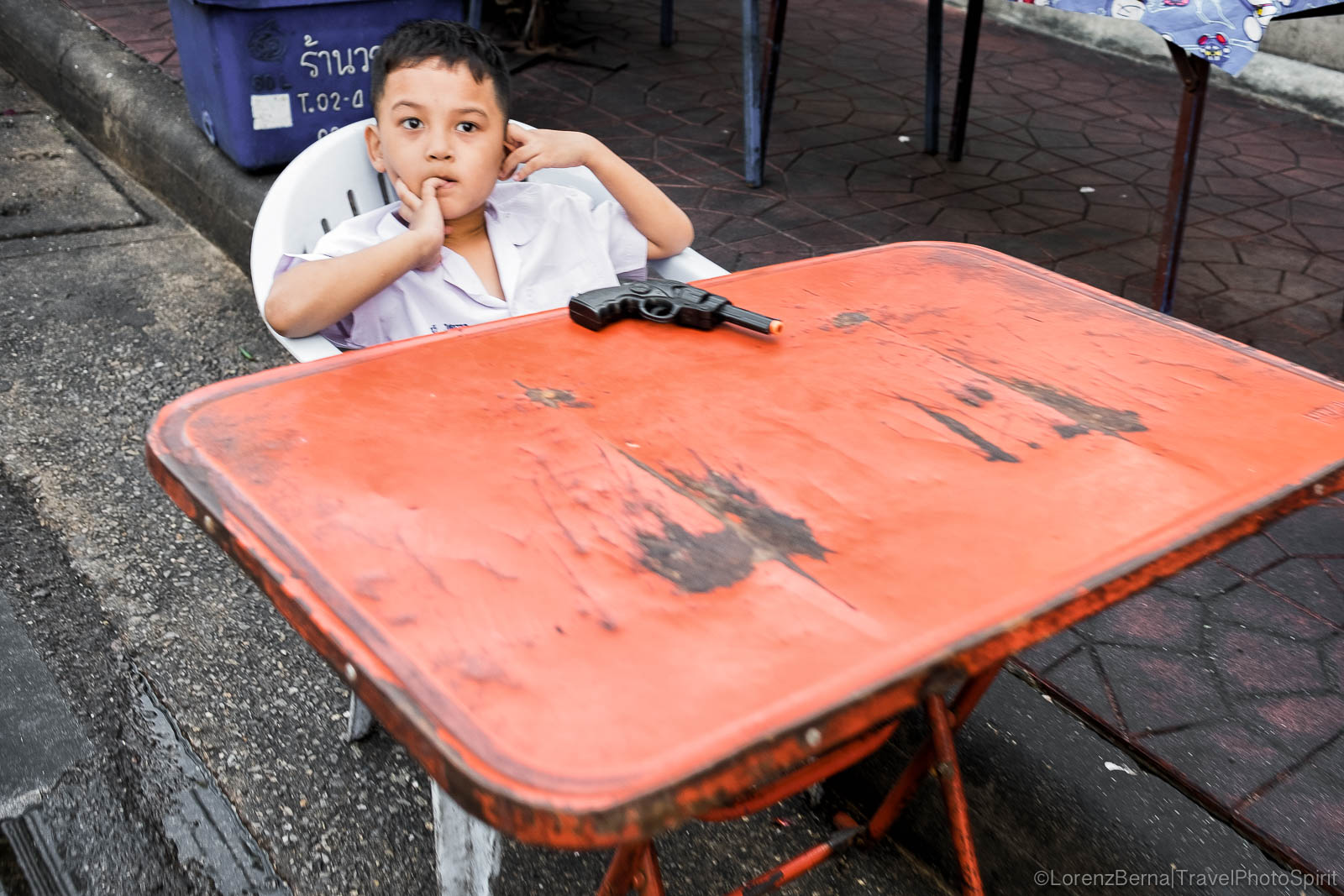 Boys game in Bangkok : a boy is sitting at a table, a plastic gun in front of him.