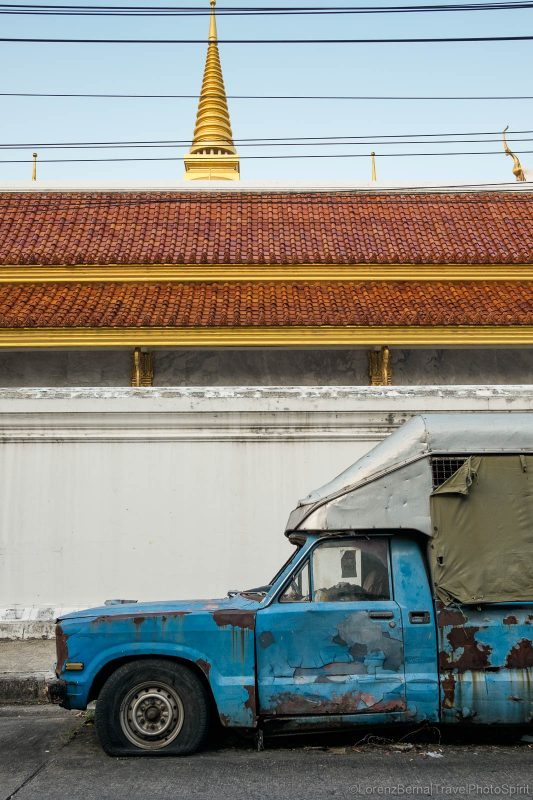 Street photography in Bangkok : an old crumbling car is parked in the backside of a temple, Thailand