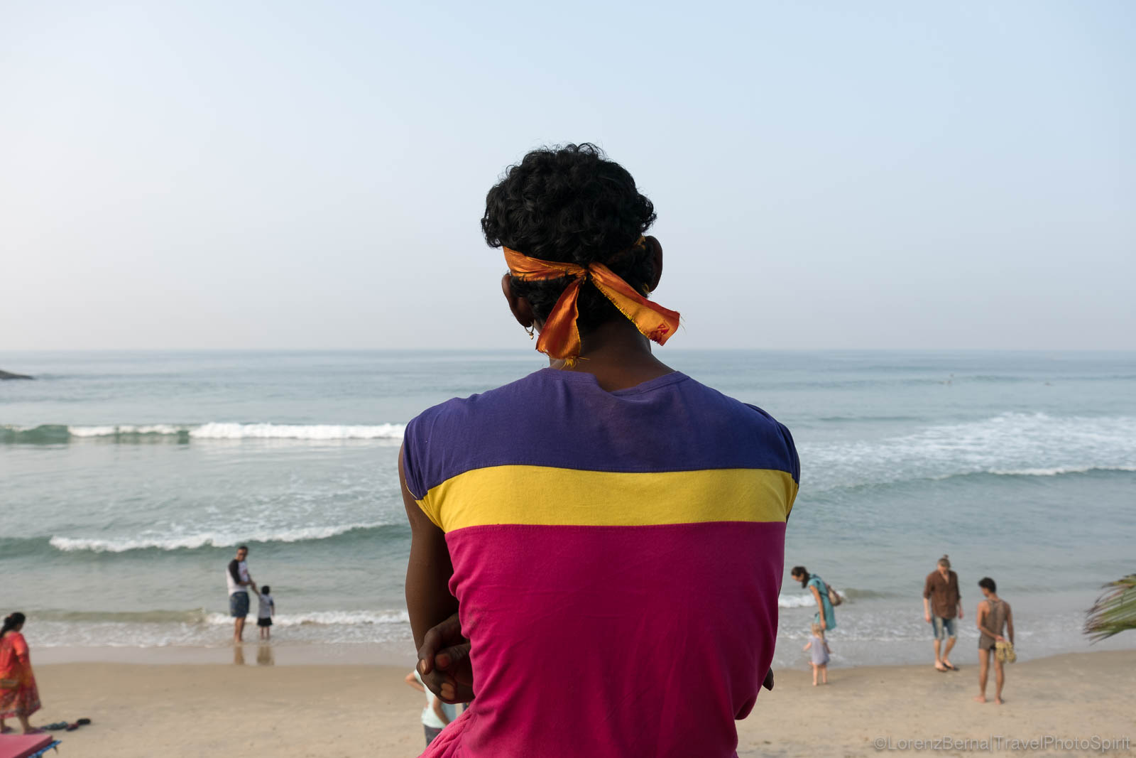 Local boy turning his back, looking at the sea in Kovalam beach, Kerala, India