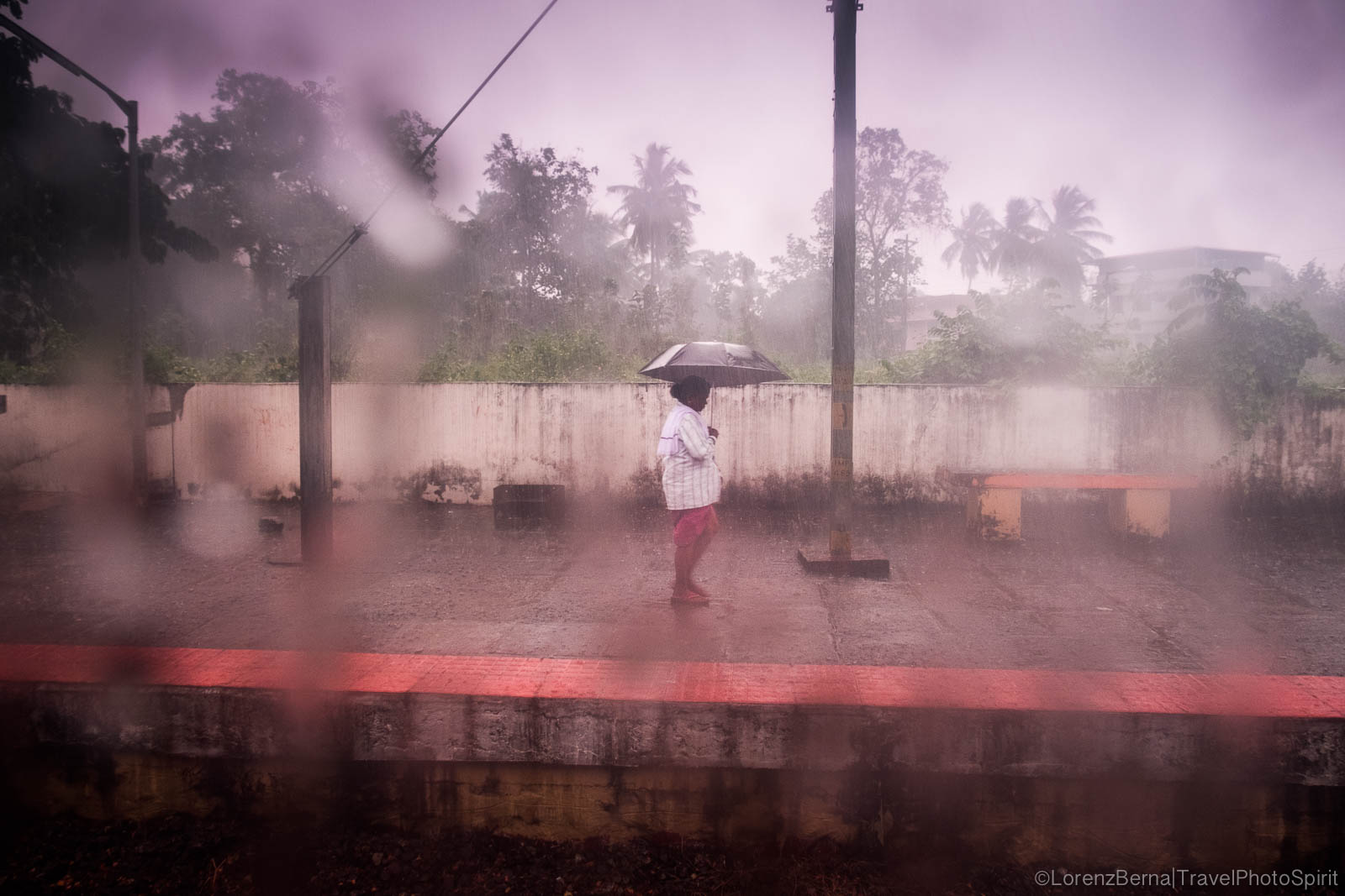 Street Photography under the monsoon rain : a man is waiting under an umbrella at a train station in Kerala, India