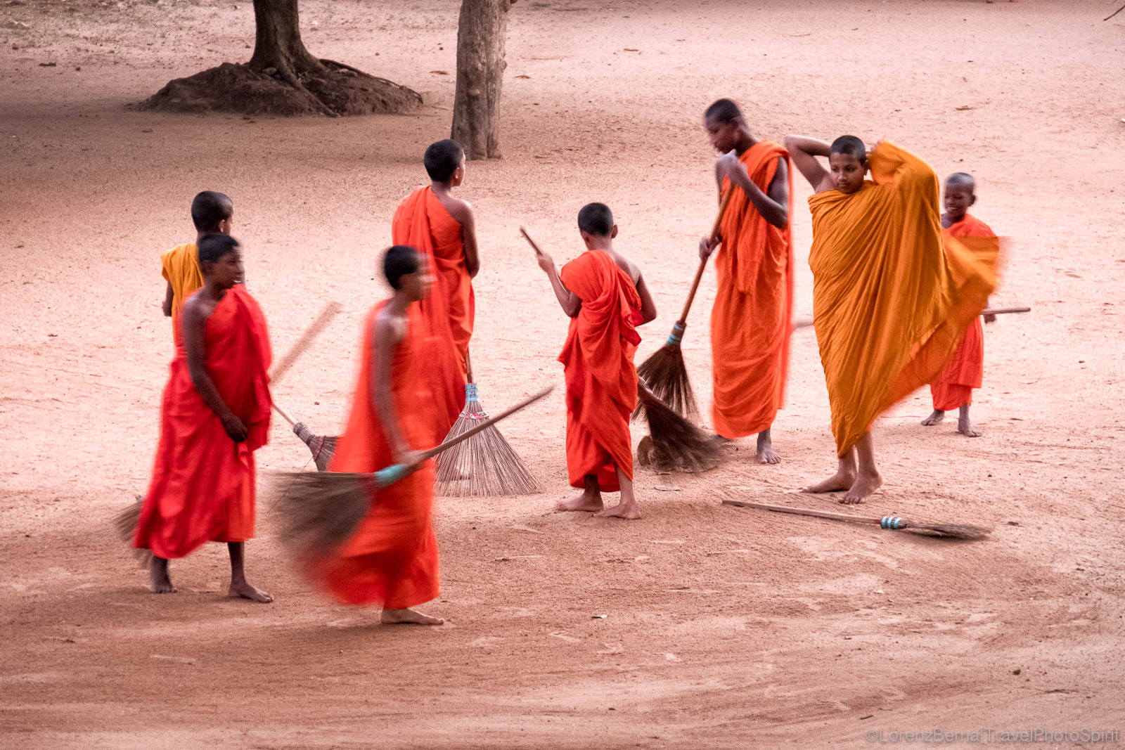 Group of monks on their morning duty, sweeping their monastery in Mihintale, Sri Lanka