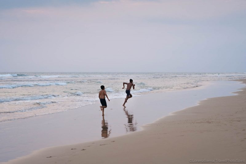 Two local kids playing on the beach of the southern coast, nearby Galle, Sri Lanka