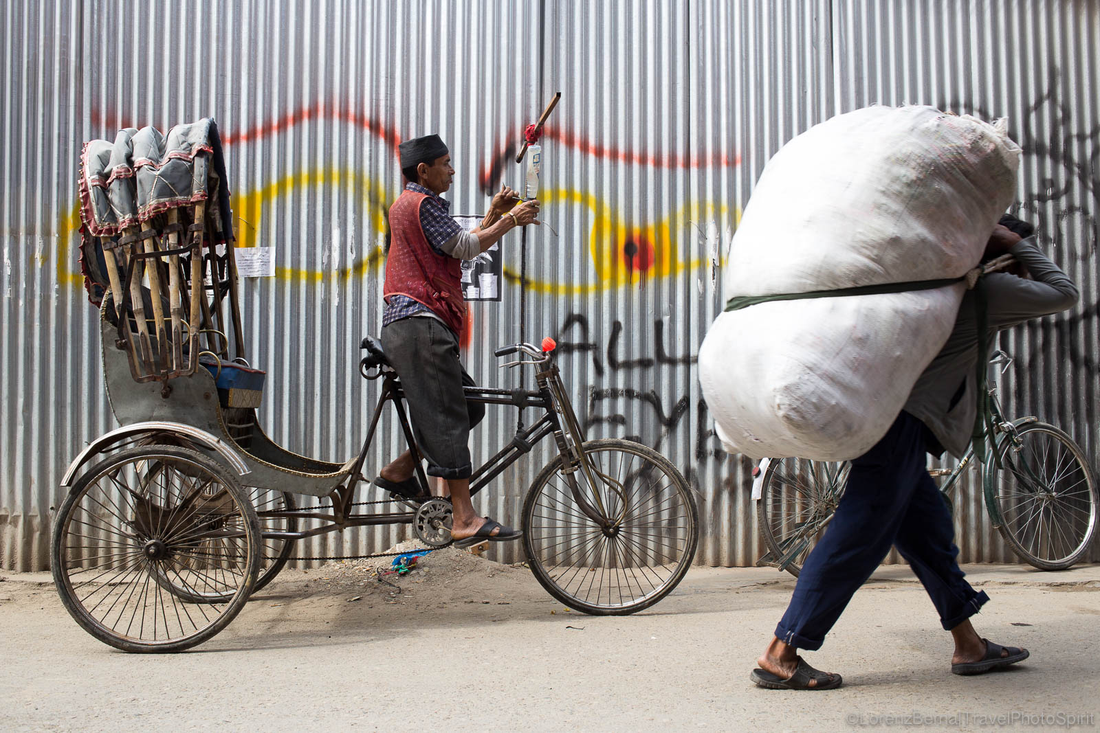 A rickshaw and a man carrying bags on his back : two different kinds of transportation in the streets of Thamel district, Kathmandu, Nepal.