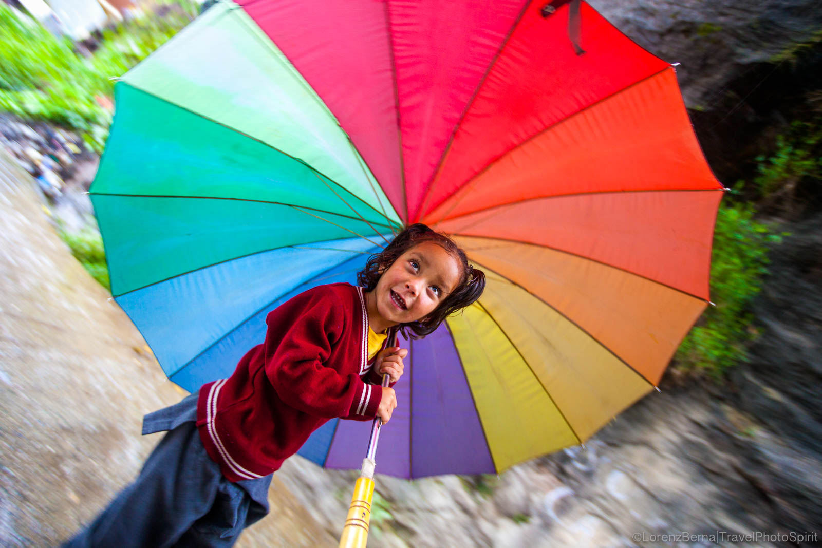 Young girl coming back from school, protected from the monsoon rain by a large multicolor umbrella in Old Manali, Himachal Pradesh - A Lorenz Berna Photography of India