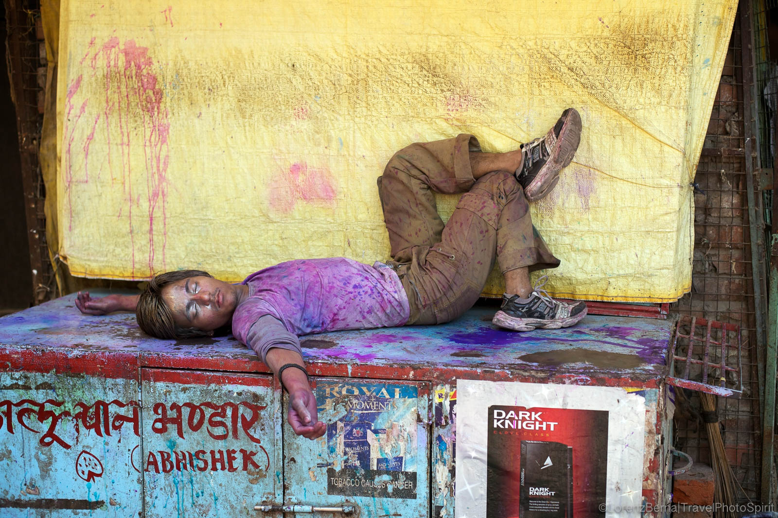 Exhausted and hungover, a young Indian Man is resting on a street stall after the Holy Festival in Varanasi, India