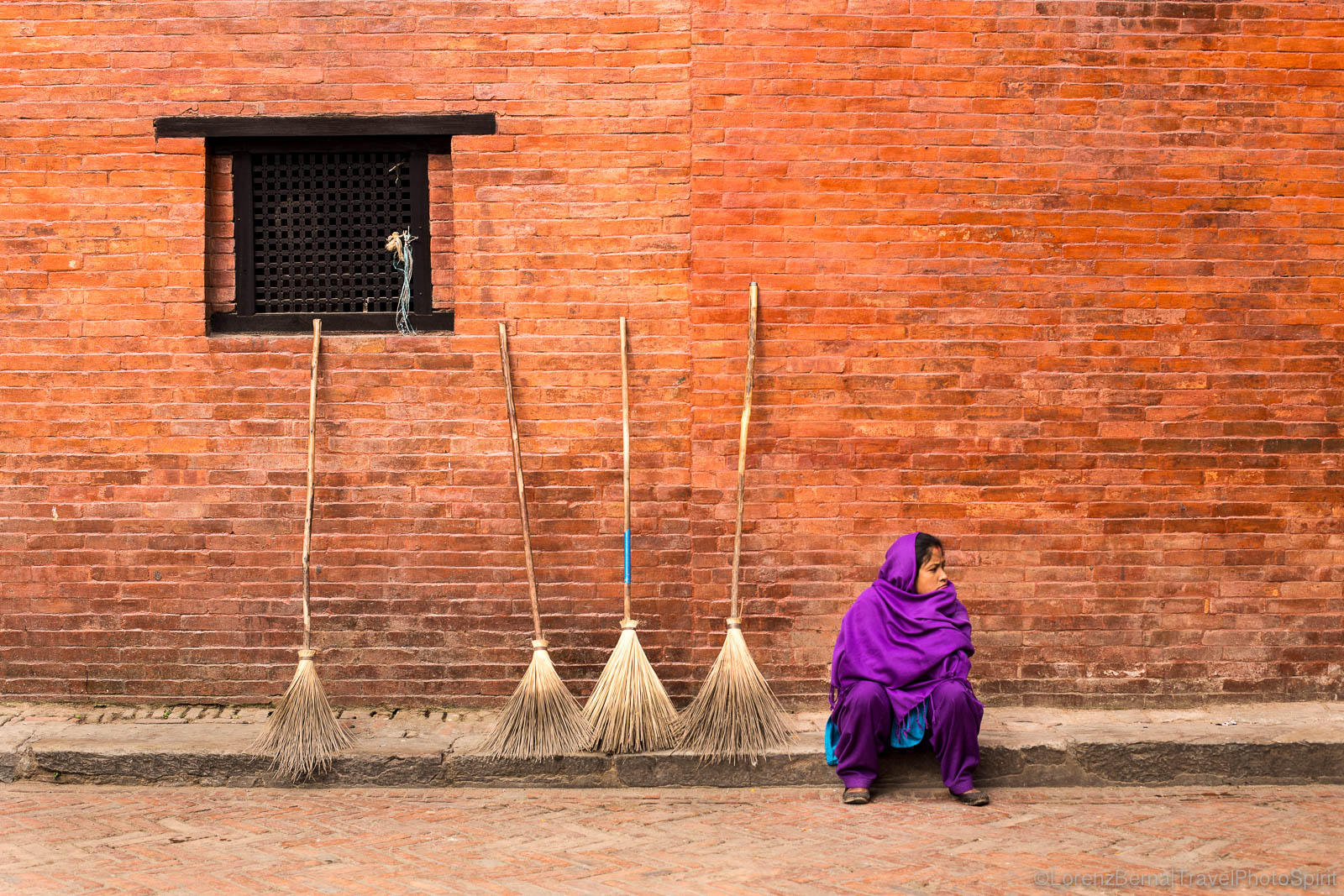 Street scene in Patan : a woman is sitting against the wall of a newari style house, next to the brooms she hopes to sell in the day.