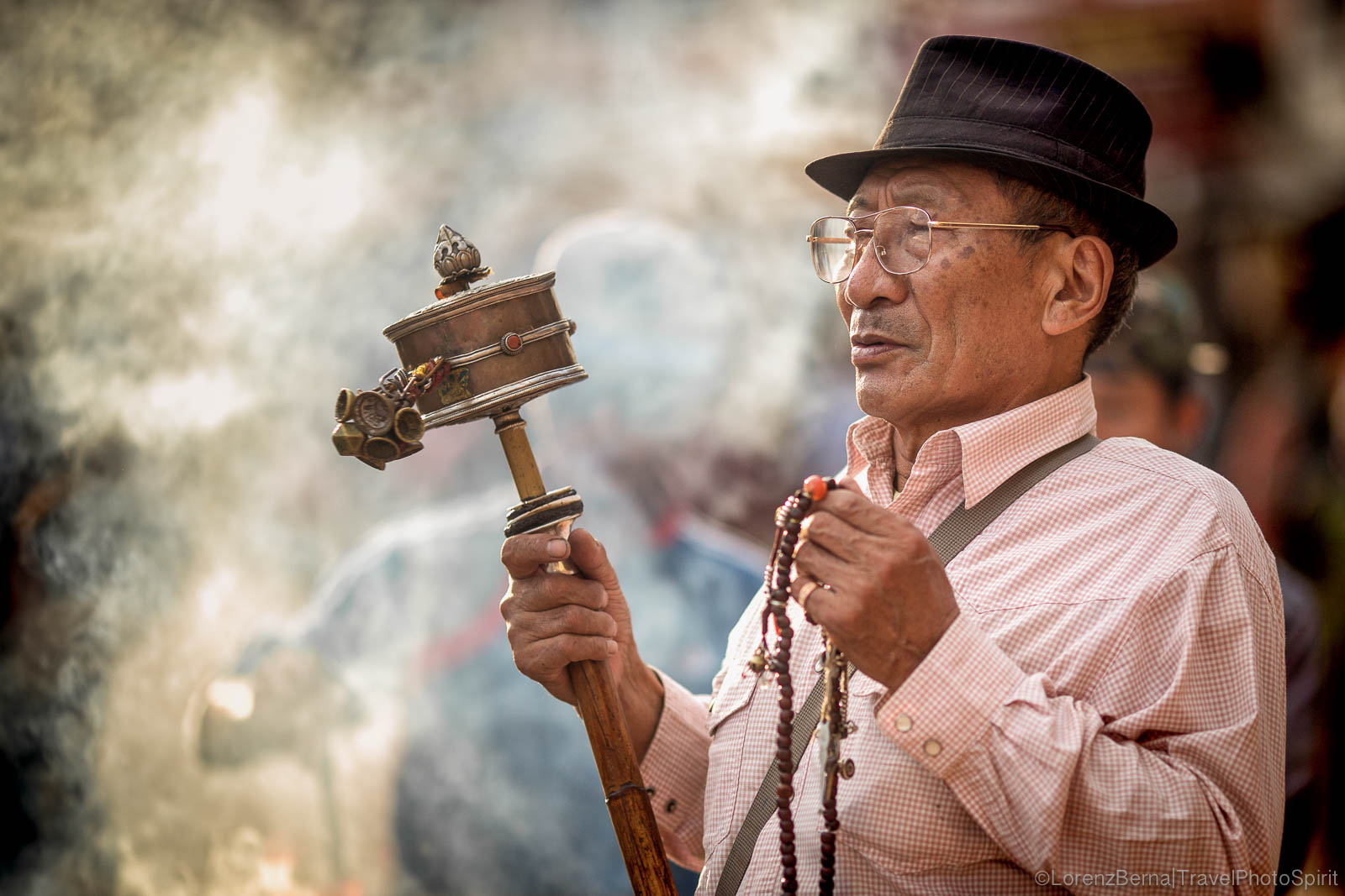 "Tibetan man praying, spinning his prayer wheel while repeating the ""Om Mani Padme Om"" mantra, in Boudhanath, Kathmandu, Nepal."
