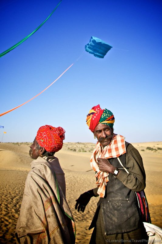 Kites flying over local men in the Thar Desert of Rajasthan, India
