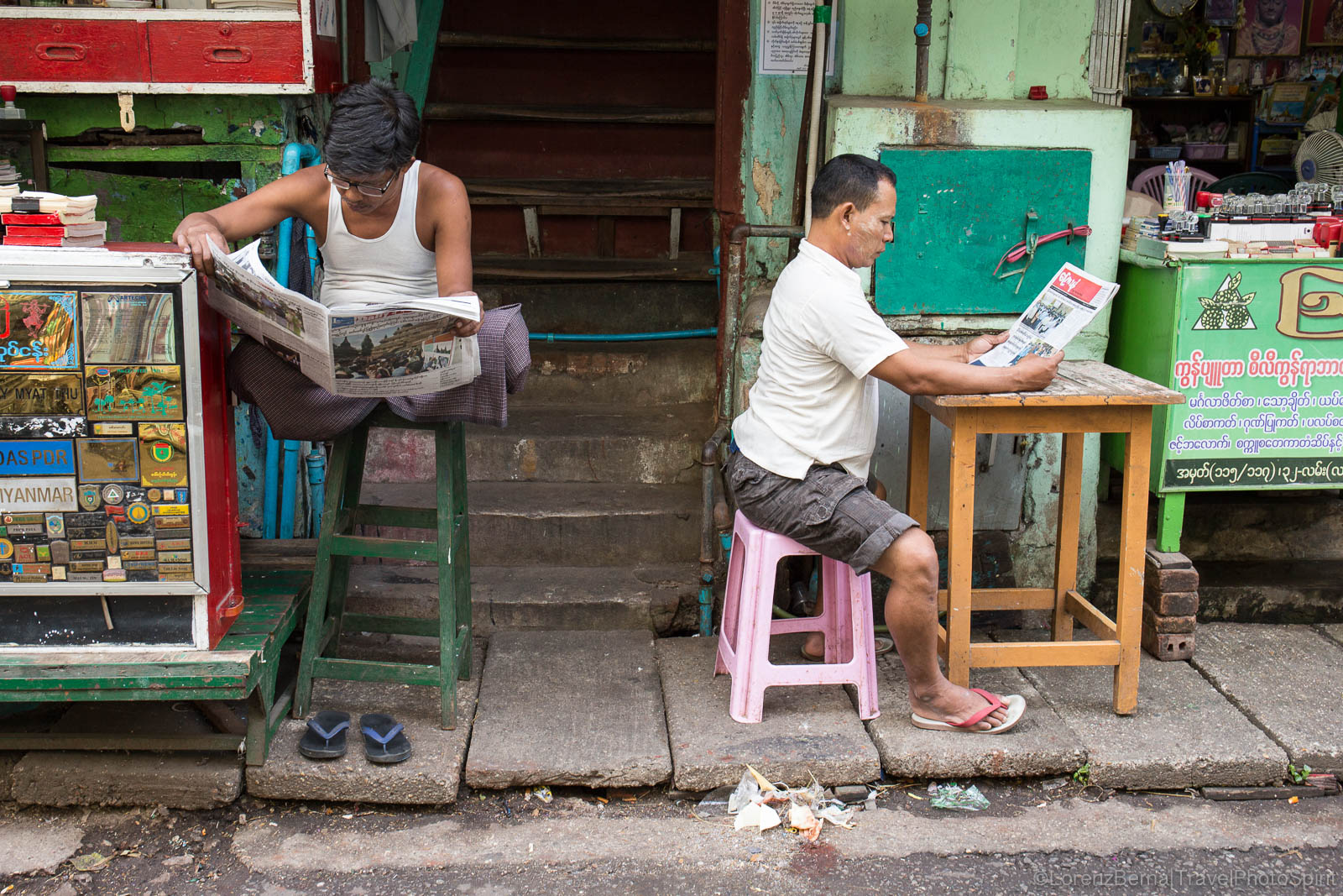 Two local men reading the News in Yangon streets.