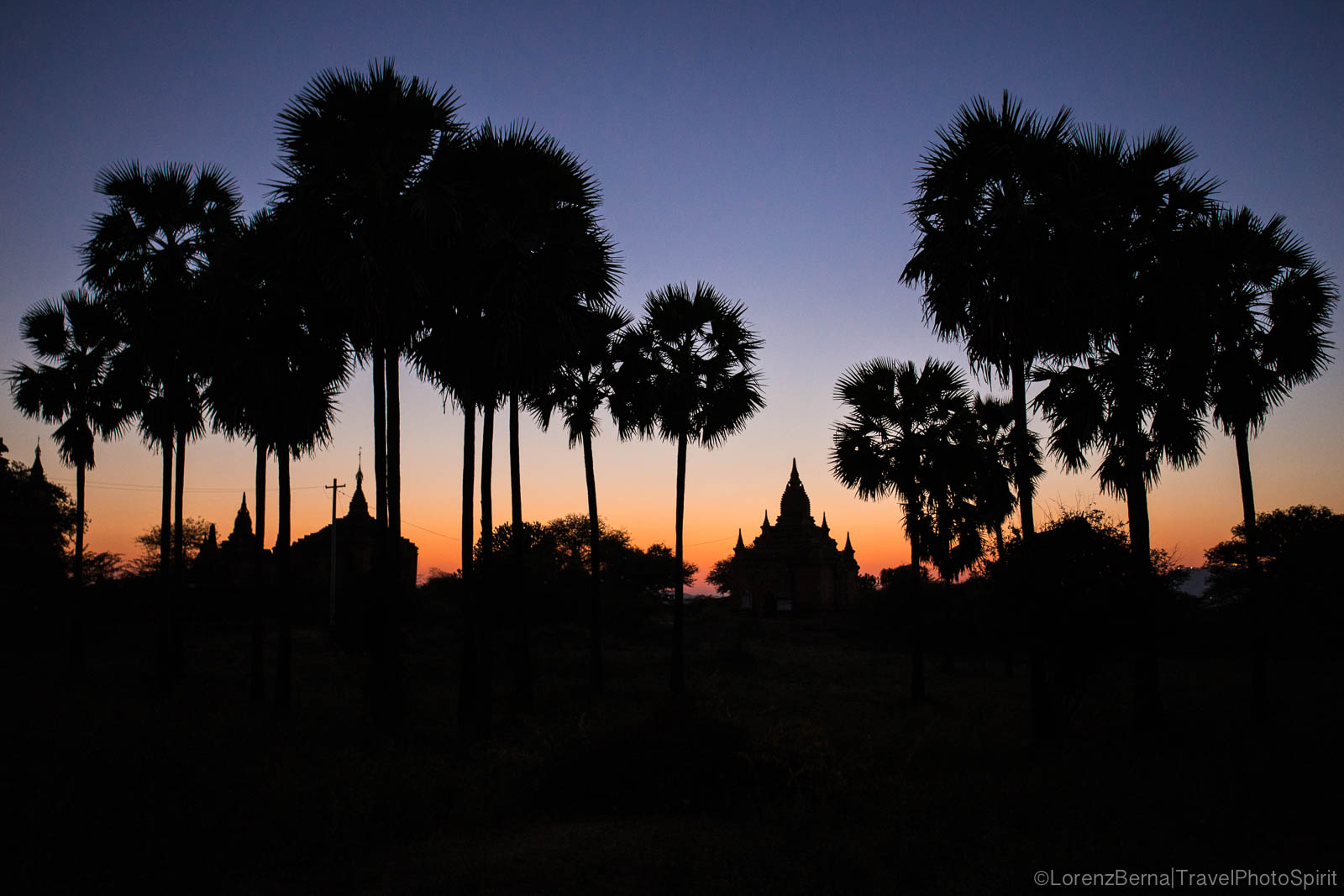 Silhouettes of pagodas and tall palms in Bagan, at dusk.