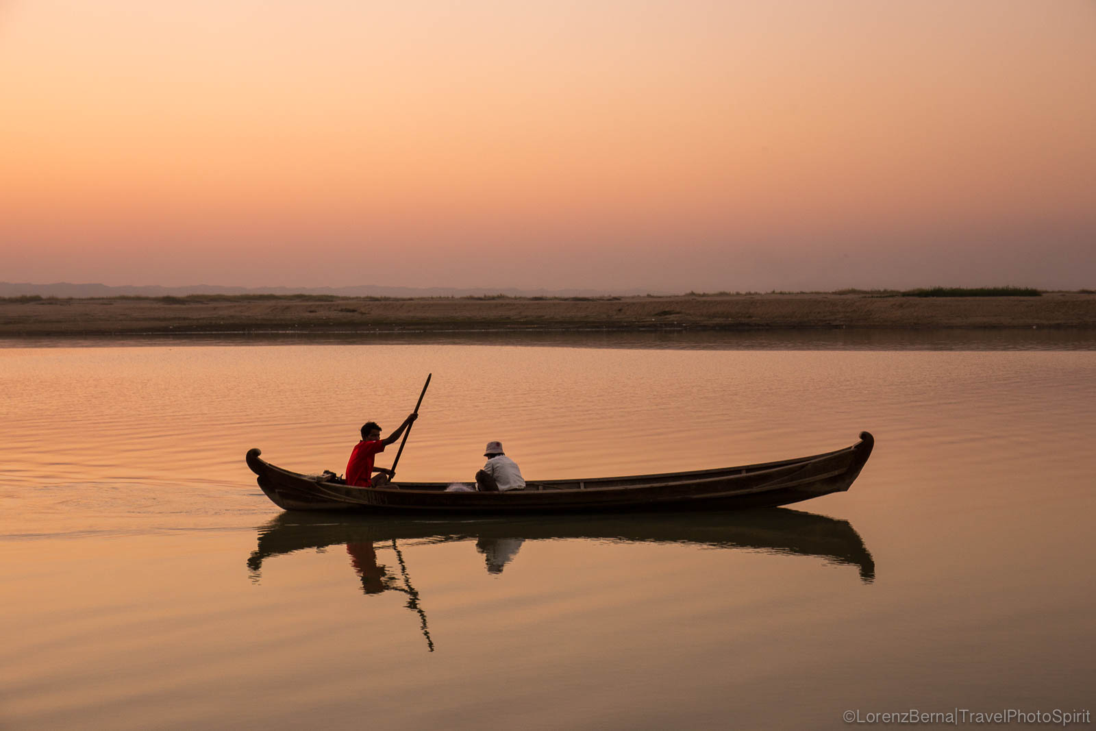 Two friends on a wooden canoe are sailing at dusk on the calm water of the Irrawaddy River - A Lorenz Berna photography of Myanmar.