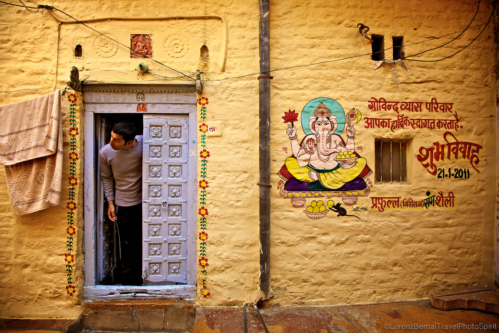 A young man is getting his head out of a colourful house painted with the spiritual figure of Ganesha, the protector, in Jaisalmer- A Lorenz Berna Photography of India