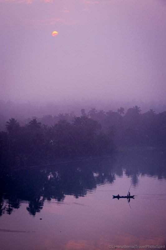 A canoe is crossing at sunrise one of the many rivers that form the backwaters in Kerala, India