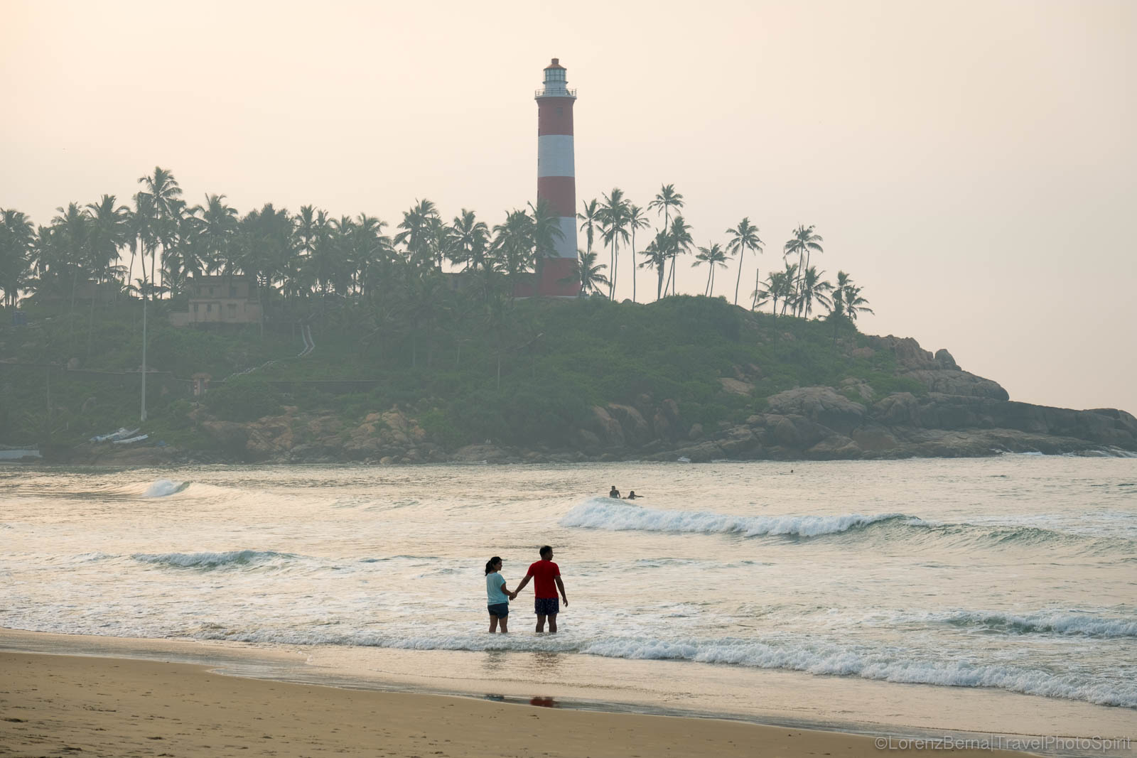 A couple on the beach of Kovalam in Kerala is waiting for sunrise, India