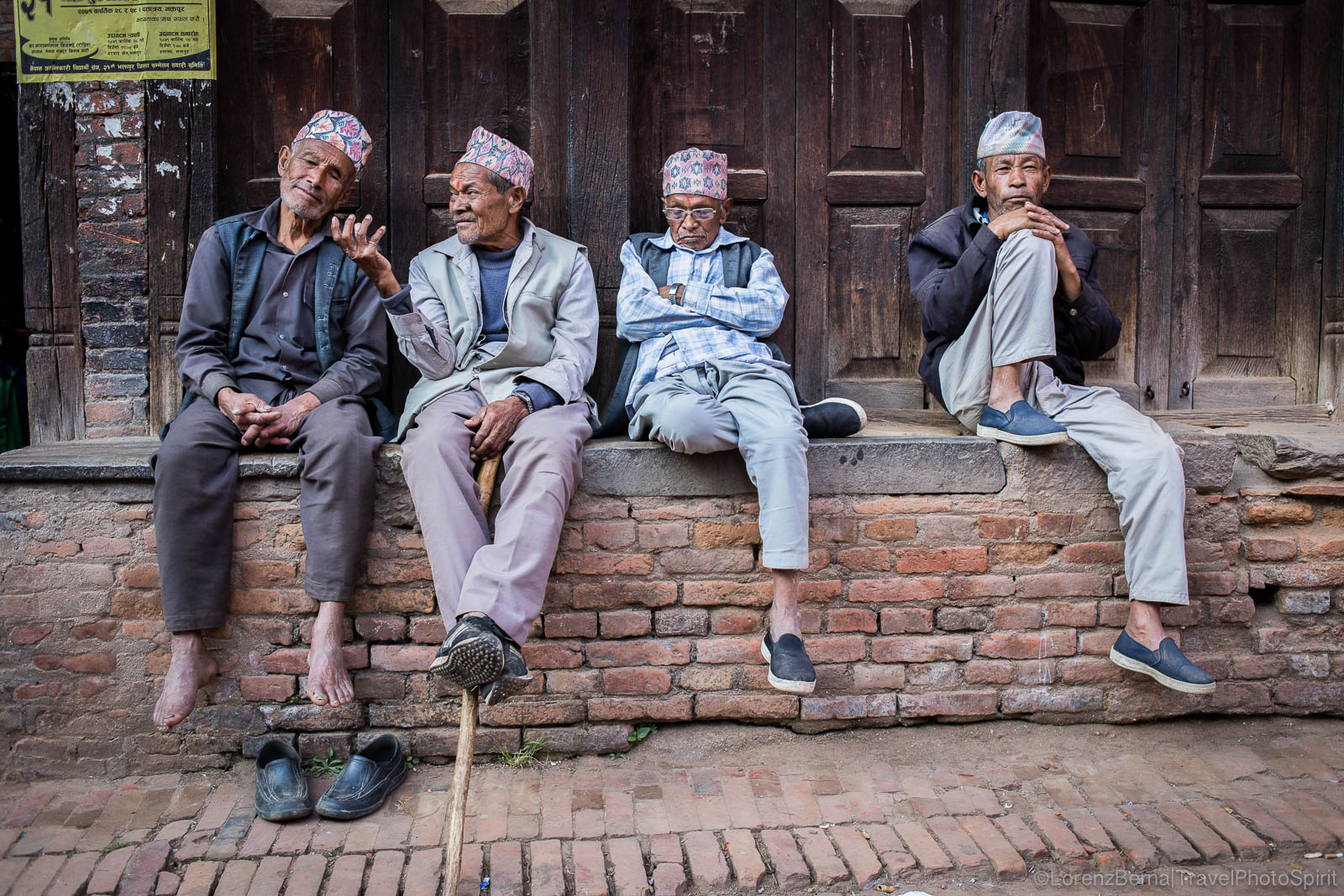 Old friends chatting on a covered brick platform in Bhaktapur, Nepal.